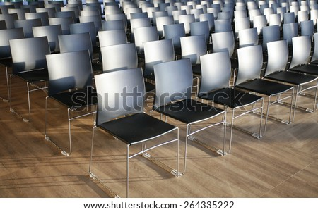 Rows of empty chairs prepared for an indoor event. Endless rows of chairs in a modern conference hall - stock photo