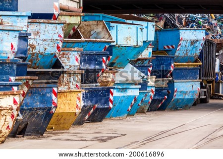 Rows of empty garbage tips stacked ready for use in collecting and disposing of household and industrial waste and rubbish in a depot or warehouse yard - stock photo