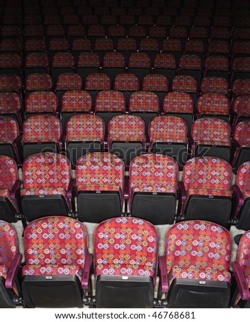 Rows of empty multicolored seats in theater. Vertical shot.