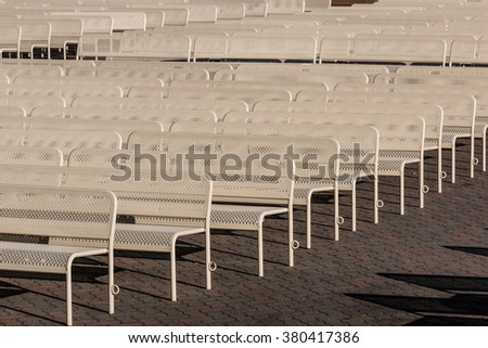 Rows of empty outdoor audience benches facing left. - stock photo