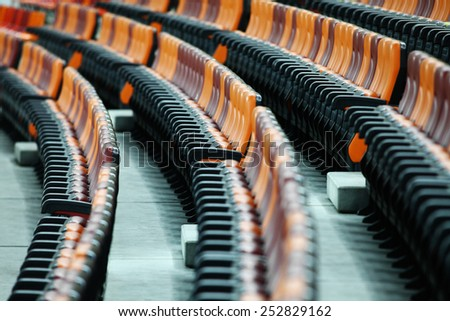Rows of empty seats of different colors in a stadium - stock photo