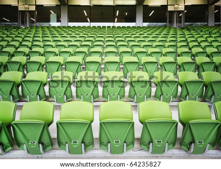 Rows of folded, green, plastic seats in very big, empty stadium. Focus on the front seats - stock photo