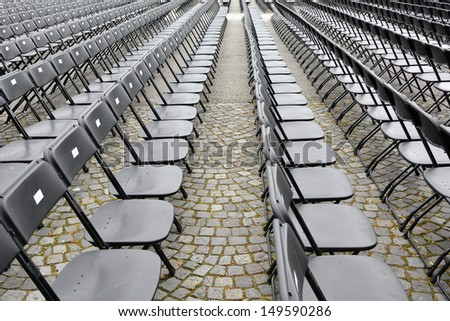 Rows of folding plastic chairs all ready for putting bums on seats at an outdoor summer music concert in town square  - stock photo