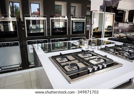 Rows of gas stoves with stainless tray selling in appliance retail store - stock photo