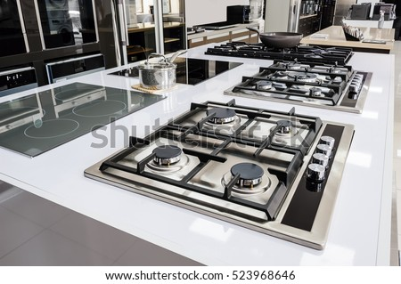 Rows of gas stoves with stainless tray selling in appliance retail store