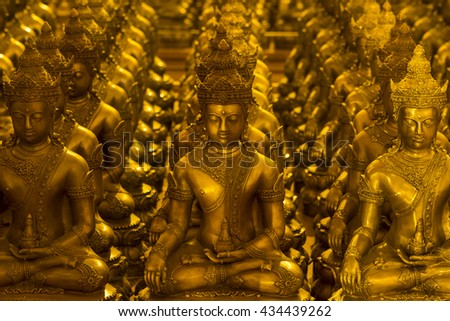 Rows of golden Buddha statues at traditional Buddhist temple in Chiang Mai, Thailand.  - stock photo