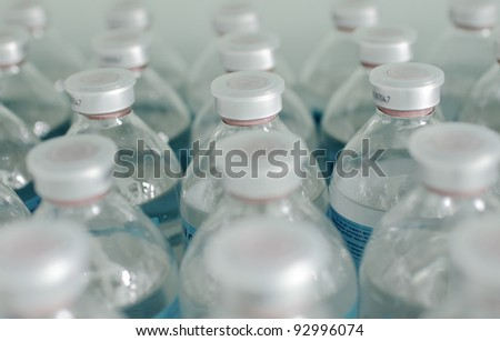rows of identical bottles. photo reflects the typical, standard, conveyor, medicine, manufacturing - stock photo