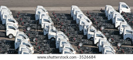 Rows of identical trucks lined up on a pier