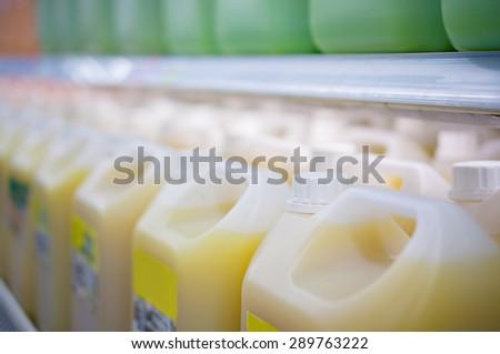 Rows of large juice bottles in fridge in supermarket - stock photo