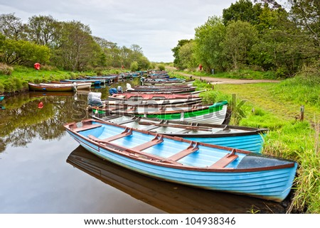Rows of little multicolored rowing boats are moored on Lough Leane (Lower Lake) Killarney, Ireland, - stock photo