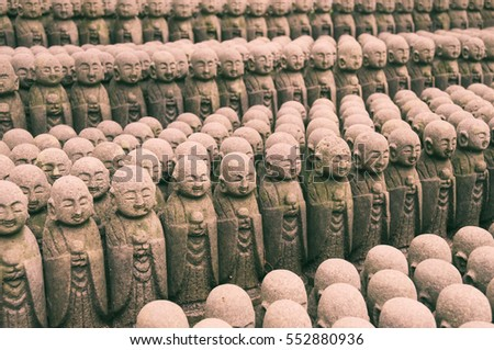 rows of many similar sculptures of Jizo deities in Kamakura, Japan