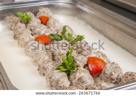 Rows of meat balls in white sauce on display at a hotel restaurant buffet - stock photo