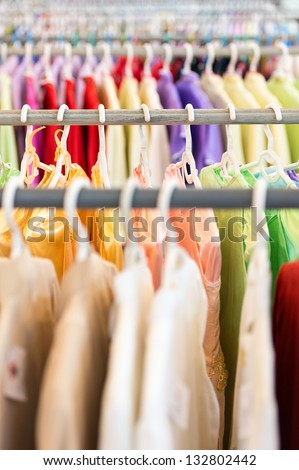 Rows of new colorful clothing on hangers at shop in foreground and background. Great choice of casual clothes of different colors. Apparel ready for sale. Going shopping. Trade and commerce.