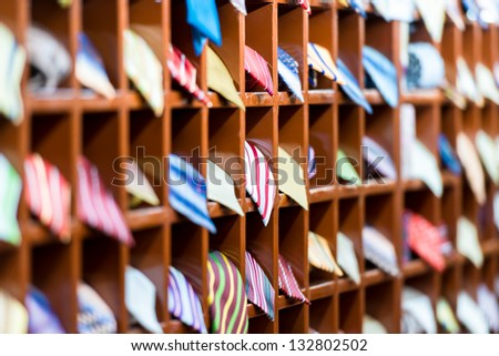 Rows of new colorful ties on shelves at shop. Great section of ties in different colors. Big choice of apparel or business style accessories ready for sale. Going shopping. Trade and commerce. - stock photo