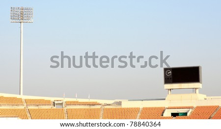Rows of orange seats on the stadium with sport scoreboard displaying clock and spot light - stock photo