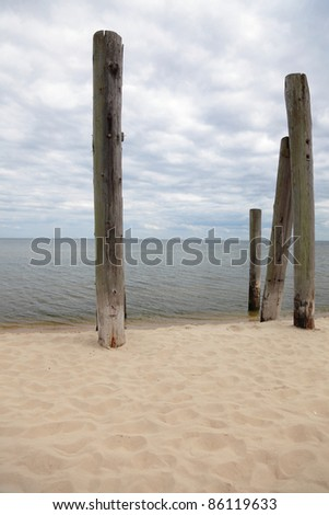 rows of piles on the sea beach - outdoor - stock photo