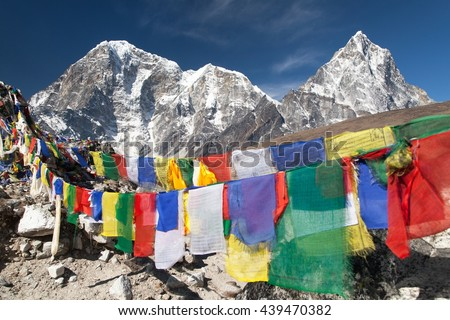 Rows of prayer flags and mounts Arakam Tse, Chola Tse and Tabuche peak, Sagarmatha national park, trek to Everest base camp - Nepal