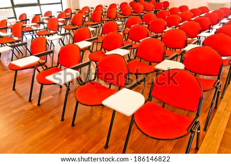 rows of red and white chairs in an empty modern conference room - stock photo