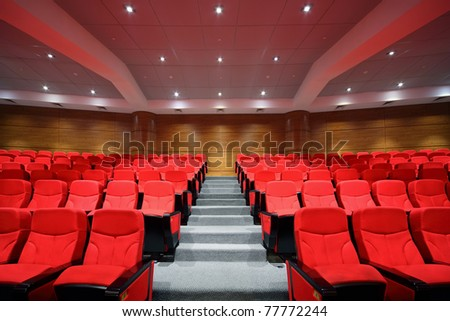 Rows of red arm-chairs are in  empty hall - stock photo