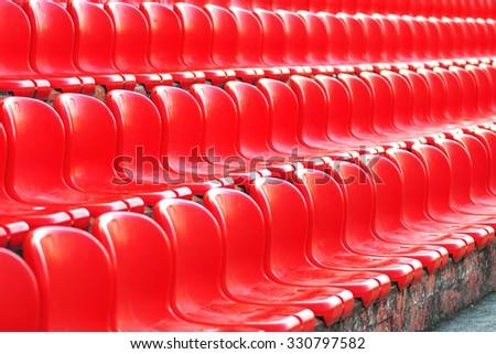 Rows of red empty plastic sport stadium seats, selective focus - stock photo