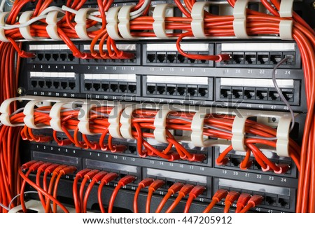 Rows of red network cables connected to router and switch hub in server room at internet data center - stock photo