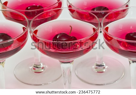 rows of red refreshing cherry cocktails on a white background - stock photo