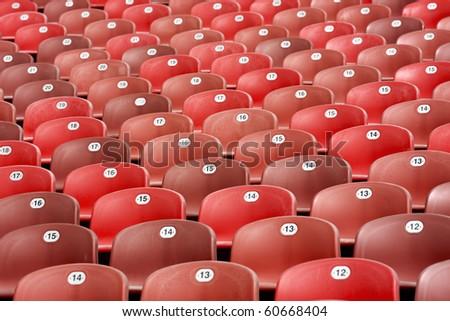 rows of red seat of stadium bleachers - stock photo