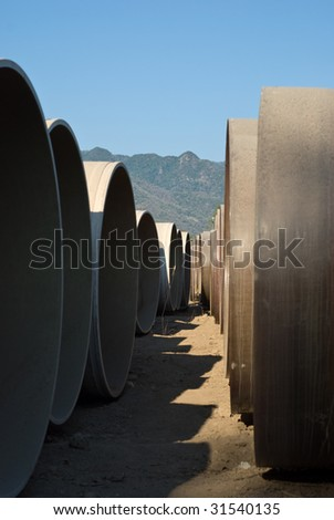 Rows of sewage piping on building site with mountain backdrop - stock photo