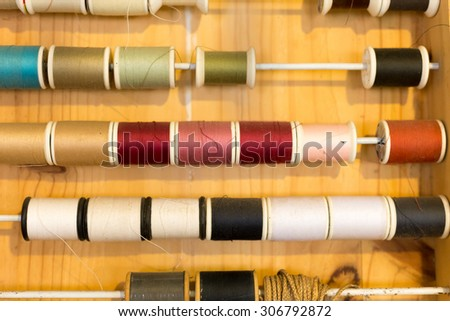 rows of sewing color threads frame on wooden table