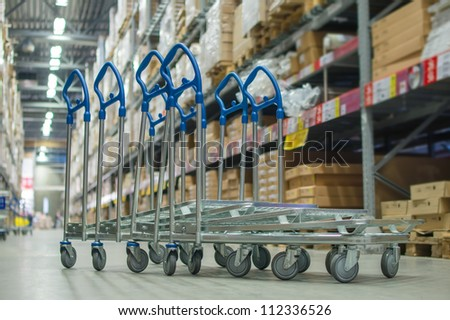Rows of shelves with boxes and storage carts in modern warehouse - stock photo