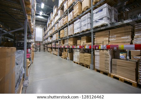 Rows of shelves with cardboard boxes on modern warehouse in store