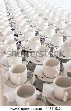 Rows of stacked teacups and saucers elevated view.
