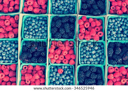 Rows of strawberries blueberries and blackberries at local farmers market - stock photo