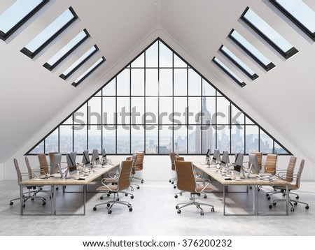 rows of tables in an office in the attic. Computers and stuff on them, white chairs. A big triangle window at the front, small roof windows above. NYC view. Concept of a modern office. 3D rendering - stock photo