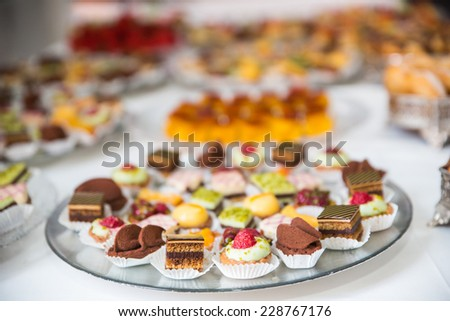 Rows of tasty looking desserts in beautiful arrangements. Mini desserts on catering buffet white tablecloth - stock photo