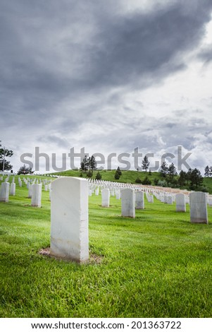 rows of tombstones in a military graveyard with bright green spring grass and dramatic storm clouds