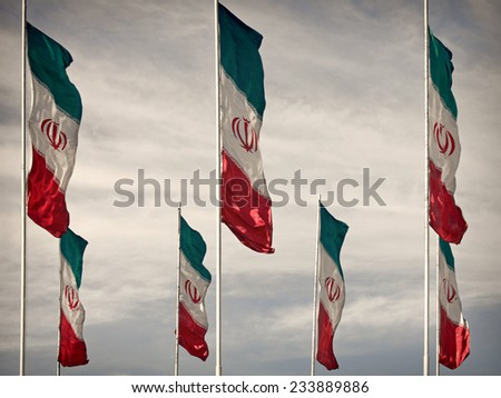 Rows of waving Iranian flags against cloudy blue sky, edited with Vintage filter. - stock photo