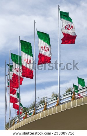 Rows of waving Iranian flags on a street bridge in Tehran against Cloudy Blue Sky. - stock photo