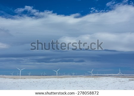 Rows of wind turbines in the winter wheat fields of Southern Alberta, Canada
