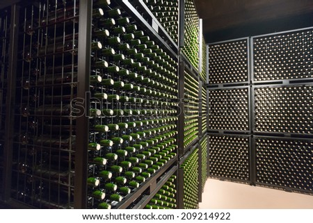 Rows of wine  bottles in winery cellar   - stock photo