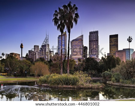 Royal Botanic Garden of Sydney city at sunset. Still water pond in the middle surrounded by plants and trees and reflecting towers of CBD architecture.