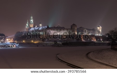 Royal castle on the Wawel hill, Krakow, Poland, over frozen Vistula river, winter night