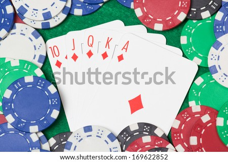 royal flush combination and poker chips on the green casino table