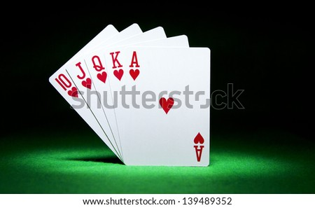 Royal Flush of Hearts playing cards balanced on green casino felt under a spotlight. Gambling concept - stock photo