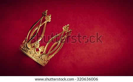 Royal gold crown on red velvet with copy space. Concept of wealth, success and kingdom. - stock photo