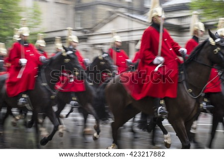 Royal guards on horseback dressed in ceremonial red coats pass in a motion-blur parade on a rainy day in London, England, UK