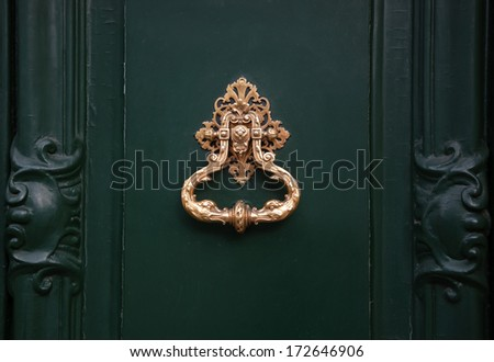 Royal style doorknocker on green door. - stock photo