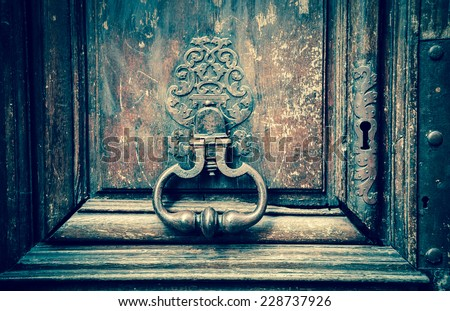 Royal style doorknocker on old wooden door. Paris, France. Aged photo. - stock photo