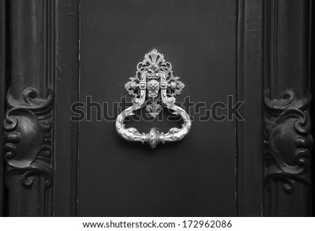 Royal style doorknocker on wooden door. Black and white. - stock photo