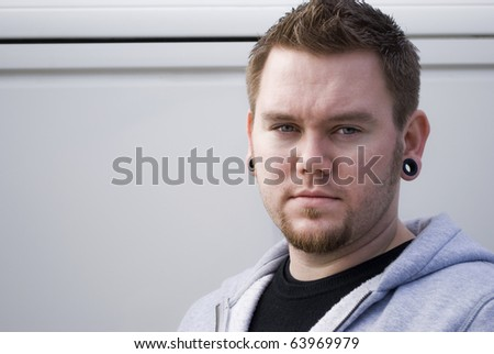 Royalty Free Stock Image of a photograph of an urban styled caucasian young man with pierced ears Looking into Camera with a neutral expression. Copy Space to the left. Shot in Natural Sunlight